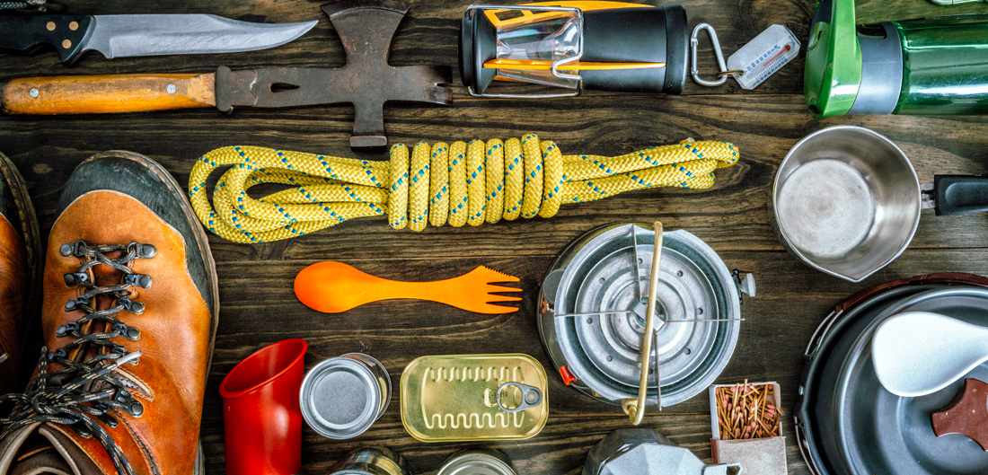 assorted camping and backpacking gear is laid on natural wood surface